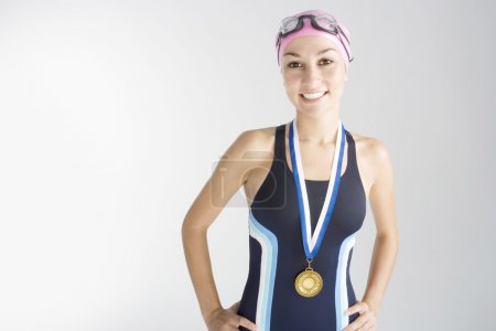 Portrait of an olympic swimmer wearing a gold medal and smiling at the camera.