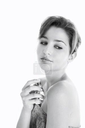 Vista en blanco y negro de una joven rociando perfume sobre sus hombros desnudos