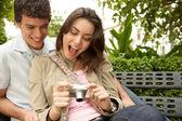 jeune couple en regardant leurs photos de vacances sur un appareil photo numérique