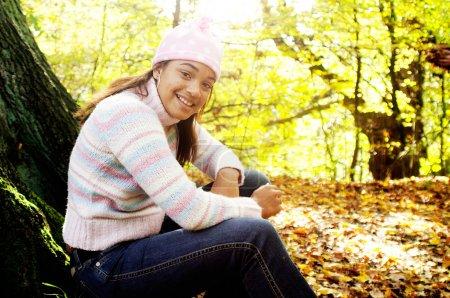 Photo pour Joyeux jeune adolescente assise sur un tronc d'arbre texturé et souriante lors de la visite d'un parc forestier d'automne lors d'une journée d'or ensoleillée pendant la saison d'automne, en plein air . - image libre de droit