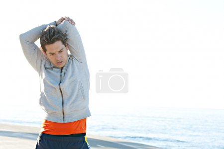 Photo for Attractive sports man stretching his arms and exercizing against a clean blue sky background, outdoors. - Royalty Free Image