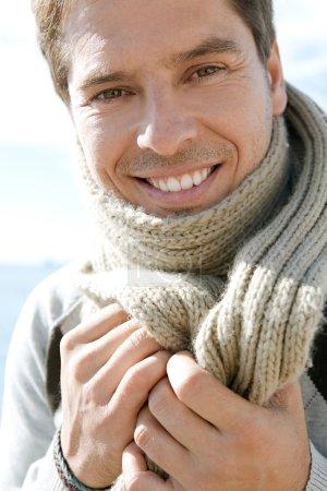 Photo pour Gros plan portrait de beauté d'un homme intelligent debout sur une plage souriant et tenant une écharpe en laine autour de son cou par une journée d'hiver ensoleillée . - image libre de droit