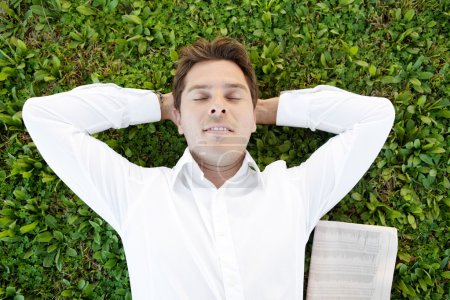 Businessman laying down on green grass