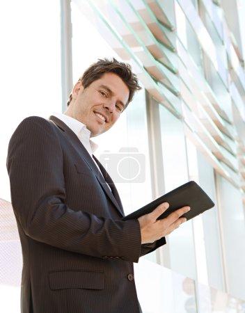 Businessman standing by a modern glass office