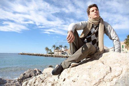 Photo pour Charmant homme intelligent assis sur les rochers d'une plage d'hiver, réfléchi avec un ciel bleu vif derrière lui . - image libre de droit