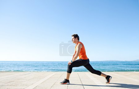 Photo for Wide profile view of a sports man figure stretching his legs on a track along the sea with the blue sky in the background and space around him. - Royalty Free Image
