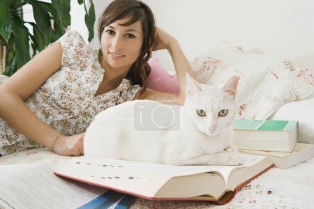 Photo for Portrait of a young attractive student pet owner laying down on her bed in her bedroom at home doing her homework with open books around her and a white cat as company, interior. - Royalty Free Image