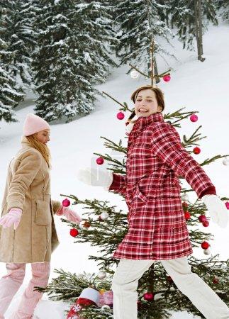 Girls running around christmas tree