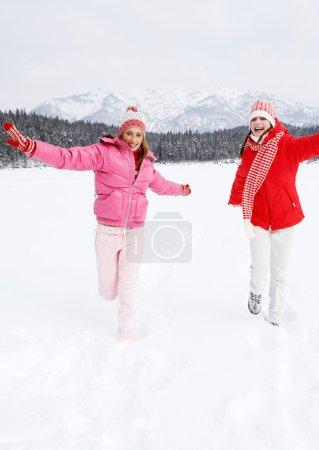 Photo pour Vue de face des deux amis joyeux jeunes femmes courir ensemble à travers un lac gelé dans le paysage de montagnes de neige pendant les vacances de ski sur une journée d'hiver ensoleillée, à l'extérieur. - image libre de droit