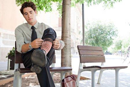 Businessman pulling up his socks