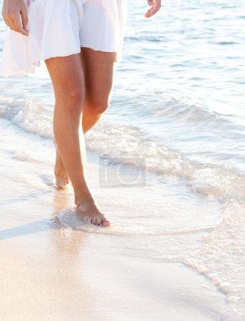 Photo pour Partie inférieure du corps d'une jeune femme marchant le long d'une plage de sable blanc au coucher du soleil, faisant des pas et se relaxant dans une destination idyllique pendant les vacances d'été . - image libre de droit
