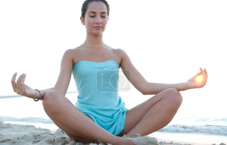 Photo for Low angle view of a healthy young woman sitting in a yoga position meditating, with the sun filtering throug her fingers in a circle during sunset on a tranquil beach. - Royalty Free Image