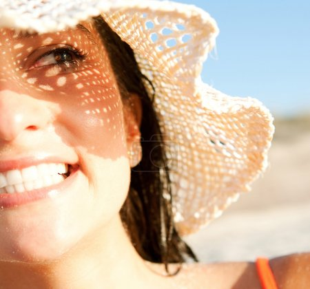 Photo for Close up portrait of an attractive woman on vacation on a beach, wearing a straw beam hat and shading her face with it creating a sun pattern on her skin. Protecting from sun rays. - Royalty Free Image