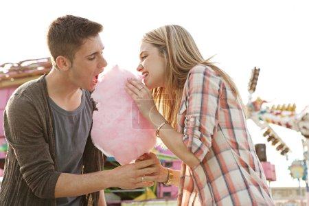 Photo pour Plaisir jeune couple mordre dans un cottong candy floss doux en même temps lors d'une visite d'un parc d'attractions au cours d'une journée ensoleillée. - image libre de droit