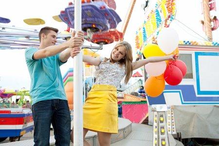 Photo pour Jeune couple d'adolescents visitant un terrain de foire amusant avec des manèges et des lumières autour d'eux, tenant des ballons, étant ludique et joyeux pendant une journée ensoleillée . - image libre de droit