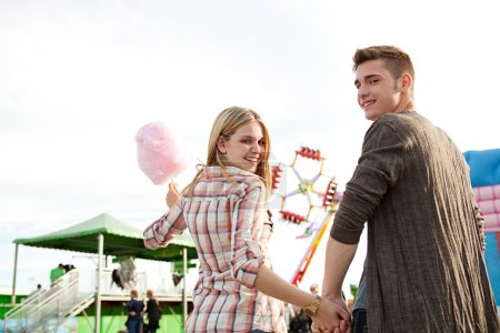 Photo for Attractive young couple holding hands and having fun in an attractions park arcade, holding a cotton candy sweet and turning to the camera smiling. - Royalty Free Image