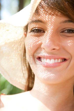 Photo pour Gros plan portrait d'une femme belle, coiffé d'un chapeau de faisceau de large paille tissée avec le soleil filtrant à travers le motif et jette une ombre de textures sur son visage, souriant. - image libre de droit