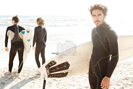 Photo pour Trois amis surfeurs sportifs debout ensemble sur une plage de sable blanc portant leurs planches de surf près du rivage lors d'une journée ensoleillée en vacances . - image libre de droit