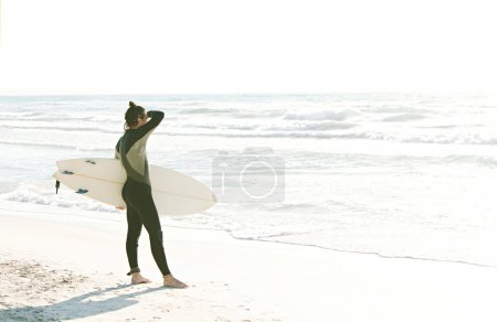 Young surfer standing