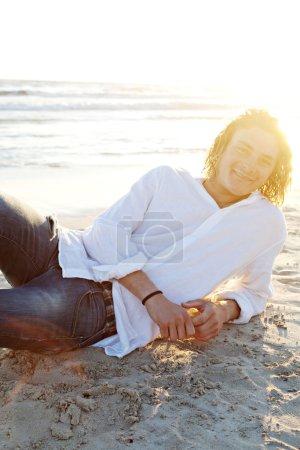 Photo pour Jeune homme profitant de vacances, allongé sur une plage de sable doré rivage, avec le coucher du soleil derrière lui et souriant à la caméra . - image libre de droit