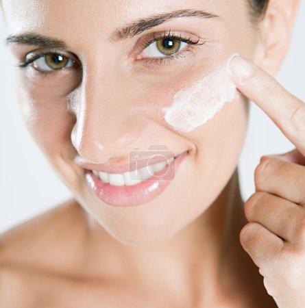 Woman applying  care cream