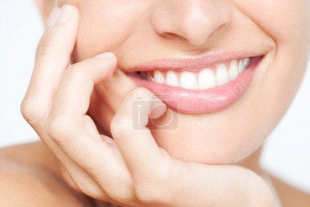 Photo pour Gros plan section beauté frontale portrait vue d'une jeune femme sourire naturel avec des lèvres roses voluptueuses appuyé sur sa main souriant avec des dents blanches, détails beauté classique à l'intérieur . - image libre de droit