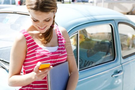 Photo for Teenager girl using her cell phone and writing a message on her smartphone leaning on a classic blue car in the city during a sunny day, smiling. - Royalty Free Image