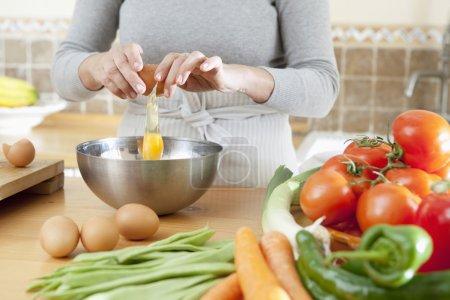 Photo pour Gros plan de détail d'une femme mains fissuration oeuf ouvrir et verser dans un bol dans la cuisine à la maison avec plusieurs légumes autour, intérieur argent. - image libre de droit