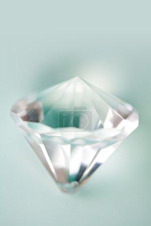 Foto de Vista de detalle de bodegón de cerca de una pieza de joyería de diamantes de gema cortada en prisma sobre un fondo azul turquesa con luz filtrándose a través del vidrio. Cristal de lujo y calidad, interior . - Imagen libre de derechos