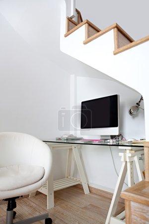 Foto de Vista de un espacio vacío moderno hogar oficina debajo de escaleras de madera, con una pantalla de computadora de escritorio en blanco. - Imagen libre de derechos