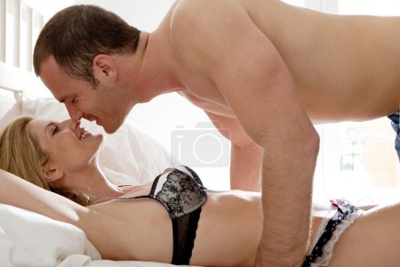 Couple kissing and hugging while laying down in bed