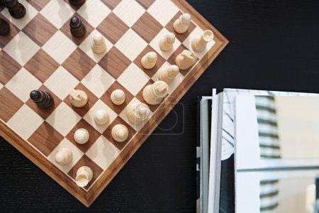 Photo pour Au-dessus de la tête encore de près vue d'un jeu d'échecs traditionnel en bois joué sur une table en bois sombre dans un salon à la maison avec une pile de livres. Loisirs et intérêts intérieurs . - image libre de droit