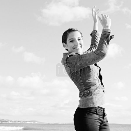 Photo for Black and white portrait of a joyful young woman feeling happy and raising her arms dancing against a sunny sky, celebrating by the sea. Fun and energetic outdoor lifestyle. - Royalty Free Image