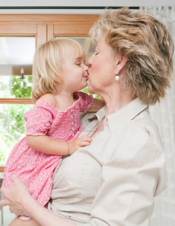 Grand mother kissing grand daughter