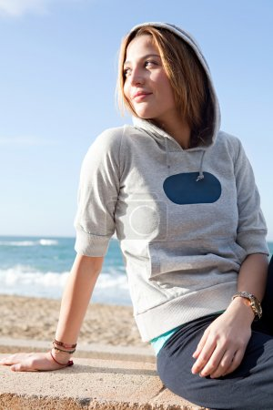 Woman sitting by a beach