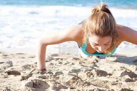 Photo pour Vue de dessus de la tête d'une jeune femme attrayante faisant des exercices push-ups sur la plage, gardant la forme pendant une journée ensoleillée . - image libre de droit