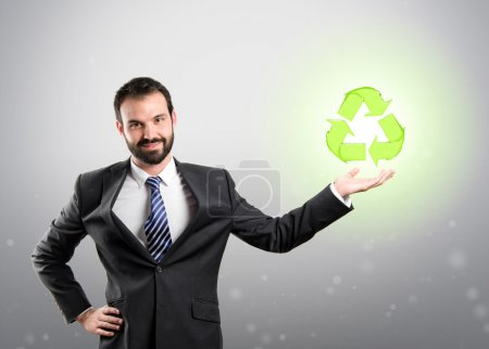Businessman holding a recycling icon over grey background