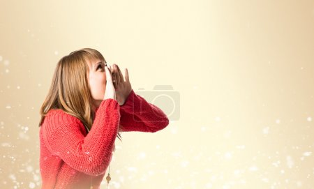 Young girl shouting over ocher background