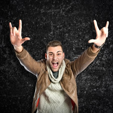 Photo for Young man doing the horn sign over black textured background - Royalty Free Image