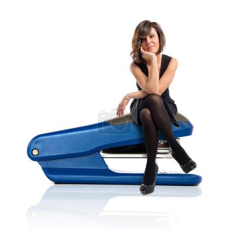 Pretty brunette woman with black dress sitting on stapler