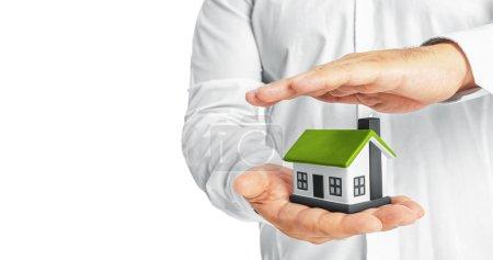 Foto de Manos cubriendo una casa modelo sobre fondo blanco - Imagen libre de derechos