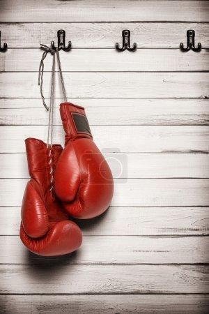 Photo pour Gants de boxe suspendus au mur en bois, y compris le chemin de coupe - image libre de droit