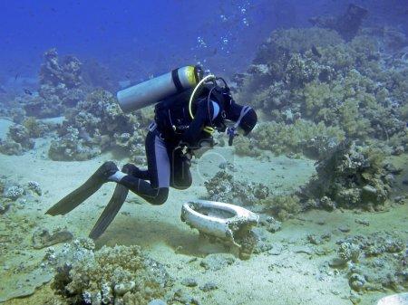 Unidentifiable diver bend over a scrap toilet unde...