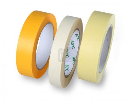 Three rolls of narrow paper tape in white, yellow and brown, iso