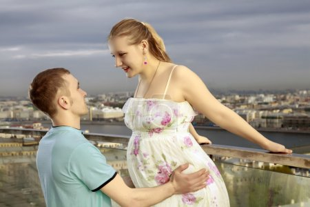 A young couple expecting a baby. A young pregnant woman walking