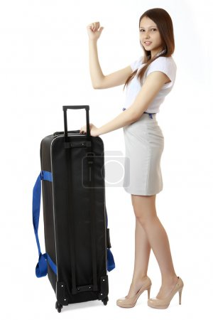 A young, slim girl teenager 16 years old, stands next to a huge, black suitcase on wheels. Girl dressed in a white blouse, high heels and a short skirt. She holds out her hand with a raised thumb.
