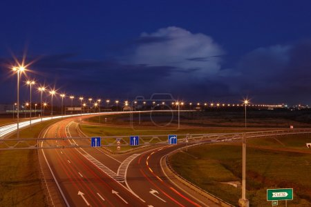 Ringway St Petersburg. Russian road at night, with markings, road signs and lighting masts. The mast lighting on night road. Electric lights in night highway. Road lighting lanterns. Russian roads.