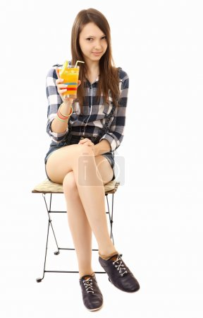 Girl teenager, caucasian appearance, brunette, wearing a plaid shirt and short denim shorts, holding a glass of drink. Teen Girl relaxing sitting on folding chair with a cocktail in hand. One person.