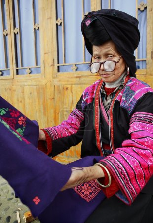 Old woman with big glasses, red Yao nationality, ethnic minorities in China, holding a blue cloth with patterns embroidered by hand, 4 April 2010. Xiaozhai Yao ethnic minority village, near Longsheng