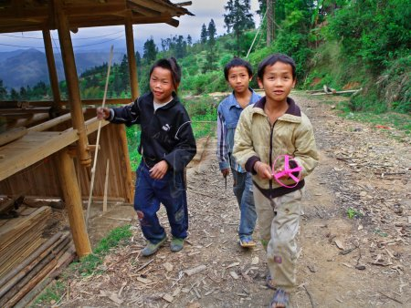 Three rural adolescents aged 12 years and stroll around the neighborhood of the village, Basha Miao Village, Congjiang County, Southeast Guizhou Province, Southwest China